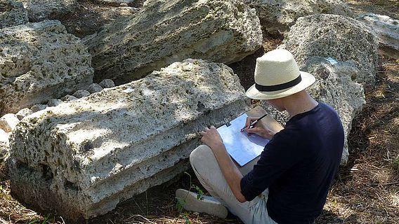 Student der Historischen Bauforschung bei der zeichnerischen Dokumentation antiker Säulenfragmenten in Olympia