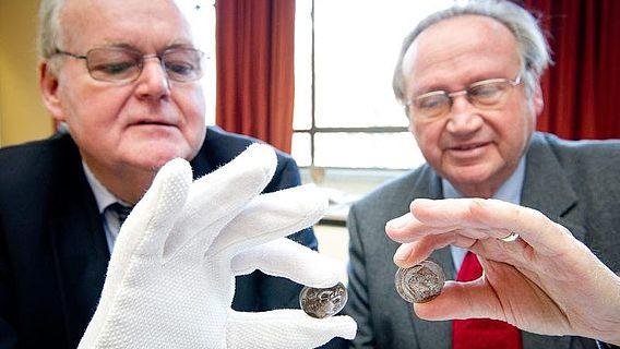 Stiftungsvorstand Professor Löwer (li.) und Stifter Dr. Trumpf begutachten die antiken Münzen. (Foto: Volker Lannert/Uni Bonn)