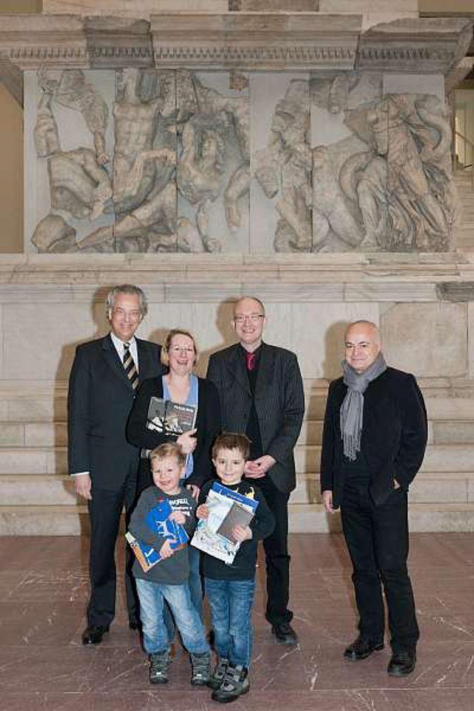 Michael Eissenhauer, Andreas Scholl und Yadegar Asisi (v. l.) begrüßen Familie Starck aus Berlin als 500.000 Besucher der Pergamon-Ausstellung (© Staatliche Museen zu Berlin, Foto: Achim Kleuker)
