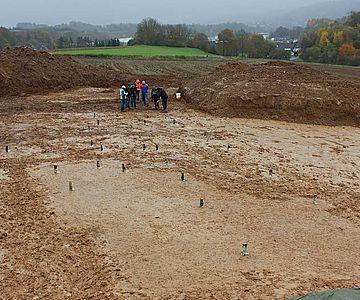 Um die Gebäudegrundrisse zu veranschaulichen, haben die Archäologen helle Birkenstammabschnitte auf die Pfostenspuren gestellt