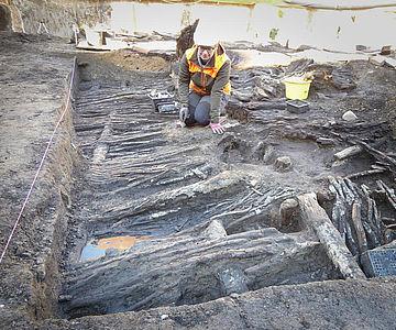 Archäologin Sarah Gonschorek legt die Hauswand des 13./14. Jahrhunderts zur weiteren Untersuchung und Dokumentation sorgfältig frei