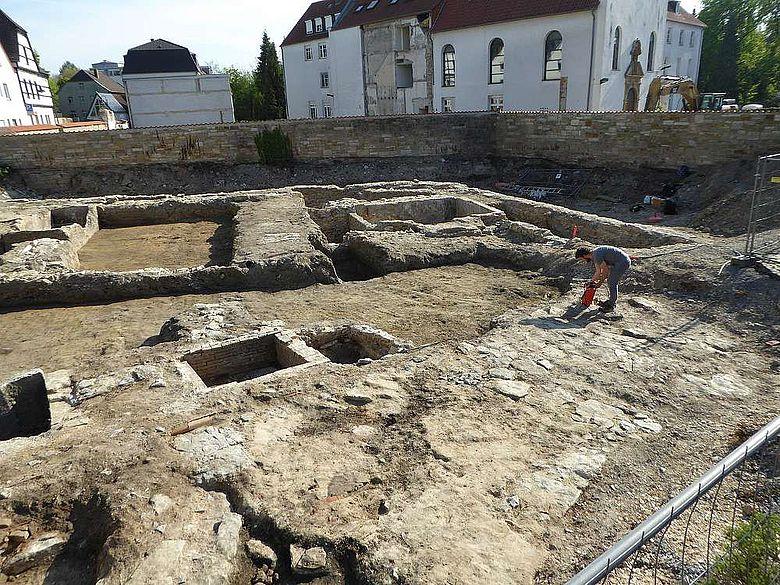 Blick über die Grabungsfläche mit Gebäudestrukturen und Grundstücksmauern