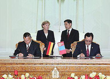 Prof. Dr. B. Enkhtuvshin und Dr. Michael Hanssler (links) bei der Unterzeichnung des Kooperationsabkommens. Im Hintergrund die Bundeskanzlerin Dr. Angela Merkel und der mongolische Premierminister Sukhbaatar Batbold (Foto: Gerda Henkel Stiftung)