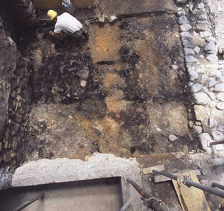 Die Archäologen am Freilegen des turmartigen Gebäudes aus dem Mittelalter. Sichtbar ist die schwarze Schicht mit verkohlten Brettern vom Dorfbrand von 1575 (Foto zvg ADB)