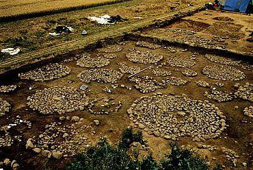 Das Gräberfeld Mühlen Eichsen im westlichen Mecklenburg während der Ausgrabung. Die Markierung der einzelnen Gräber durch Steinkreise ist eine seltene Erscheinung, zeigt aber zugleich, dass sich die Wertschätzung der Toten nicht nur in der Ausstattung mit Grabbeigaben widerspiegeln muss. (nach MÜLLER 2002, 221 Abb. 1)