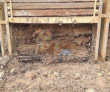 Baugrubenprofil, in dem noch Reste der als Unterbau dienenden Balken und der darauf ruhenden Mauer zu sehen sind