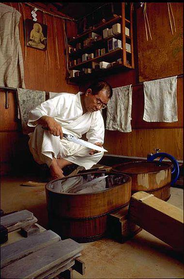 Abb. 4: Der Schwertpolierer Takushi Sasaki mit einer Saxklinge des 6. Jh. n. Chr. aus Bad Krozingen. Dieses einschneidige Kurzschwert war die erste frühmittelalterliche Klinge, die in Japan auf die althergebrachte Weise poliert worden ist. Auch in Europa waren die Schwertschleifer und Polierer bis ins 20. Jh. hinein Spezialisten, die eine meist 4-jährige Lehrzeit zu absolvieren hatten. (Foto: Kenichi Nakajima, für National Geographic Magazine 5, 1999, japanische Ausgabe).