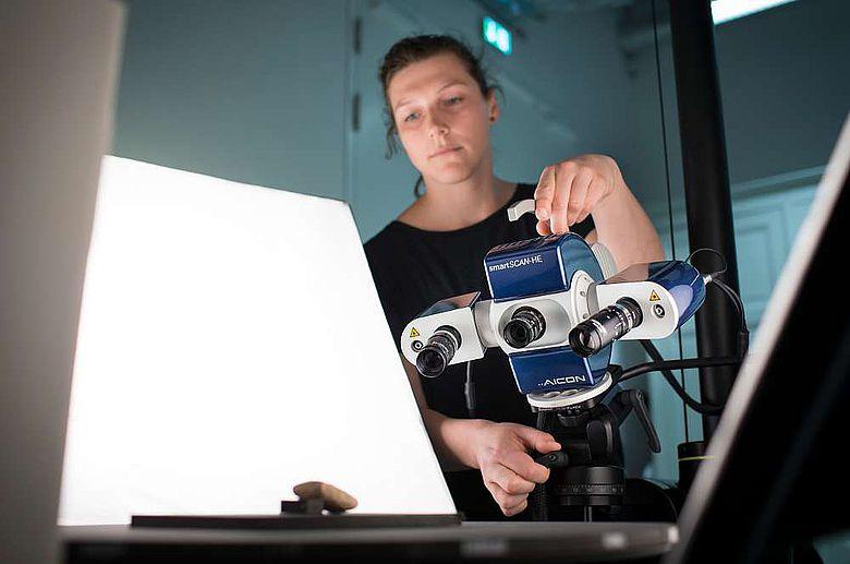 Mitarbeiterin des Zentrum für Digitale Kulturgüter in Museen (ZEDIKUM) digitalisiert eine Tontafel mithilfe eines Streifenlichtscanners