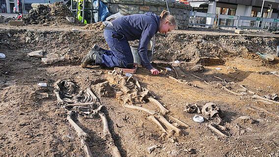 Archäologin legt Skelette frei