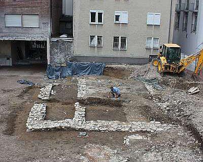 Eindrucksvoll sind die baulichen Spuren aus der Paderborner Marktsiedlung mit den Grundmauern des mächtigen Steingebäudes sowie einem Ofenfundament und einem Brunnen im Vordergrund. Im Hintergrund ist ein vollständig erhaltener feuerfester Speicher aus dem Mittelalter zu sehen. (Foto. LWL/Spiong)