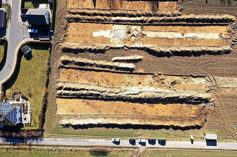 Das Drohnenfoto zeigt Streifen, in denen der Bagger den Oberboden entfernt hat.