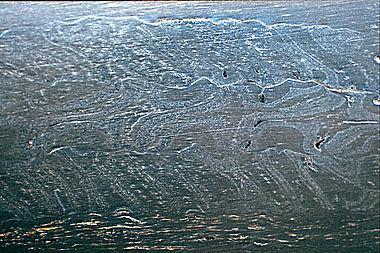 Abb. 3: Schweißmuster in einer »wurmbunten« Spathaklinge aus dem 6. Jahrhundert n. Chr. aus Neudingen. Die Klinge wurde 1999 in Japan poliert. Das Muster beruht auf der gegenläufigen Torsion von drei Stahlstäben, die aus jeweils 7 Lagen von 2 im Wechsel angeordneten Werkstoffsorten bestehen. Es wurde nicht durch Ätzen hervorgehoben. Solche Muster, die an zahlreichen herkömmlich konservierten Klingen vorkommen, werden in der archäologischen Literatur häufig missverständlich als »Damaszierung« bezeichnet. Am oberen und unteren Bildrand ist die feine Lagenstruktur des Schneidenstahles zu erkennen, wie sie auch an japanischen Schwertklingen späterer Zeitstufen vorkommt. Klinge: Neudingen, Kreis Schwarzwald-Baar, Gräberfeld im Gewann »Auf Löbern«, Grab 75, o. Inv. Nr.. Verbleib: Zentrales Fundmagazin der Bodendenkmalpflege Baden-Württemberg, Rastatt. (Foto: Stefan Mäder)