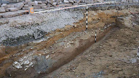 Pflasterung aus Kalksteinbruchstücken, die den Rest einer spätmittelalterlichen/ frühneuzeitlichen Marktplatzoberfläche darstellt