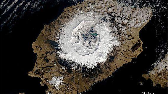 Auf der Insel erhebt sich Okmok als breiter Schildvulkan 1073 Meter über dem Meeresspiegel
