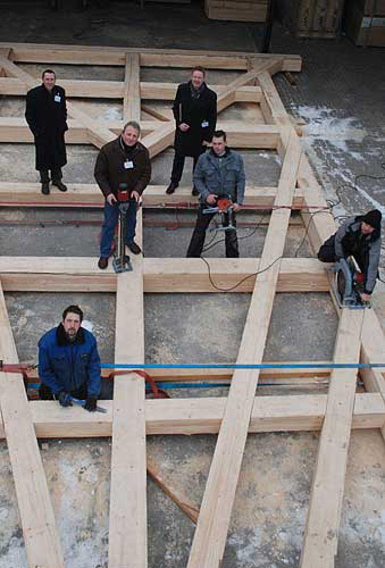 LWL-Chefarchäologe Prof. Dr. Michael Rind und Museumsleiter Dr. Josef Mühlenbrock nehmen die Fachwerkkonstruktion von Zimmermeister Bernd Krupka und seinen Kollegen entgegen. (Foto: LWL)