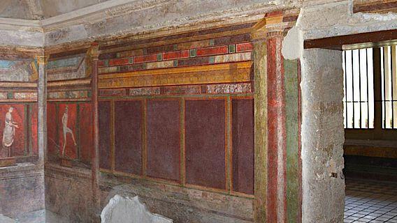 In der Villa dei Misterii (Pompeji) bilden die dekorativen und figürlichen Elemente der Wand- und Bodengestaltung im Zusammenspiel mit der Architektur ein komplexes Raum-Bild-Ensemble