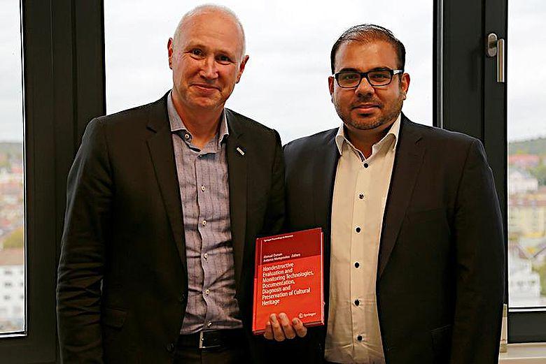 Prof. Dr.-Ing. Dieter Leonhard, Präsident der htw saar, erhält ein Exemplar von Prof. Dr.-Ing. Ahmad Osmans Buch