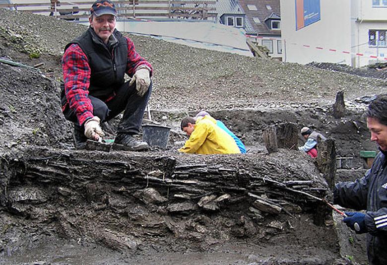 Die Grabungsmitarbeiter Hans-Dieter Tollkötter und Petra Hendrix legen den 600 Jahre alten Zaun frei. (Foto: LWL/Spiong)