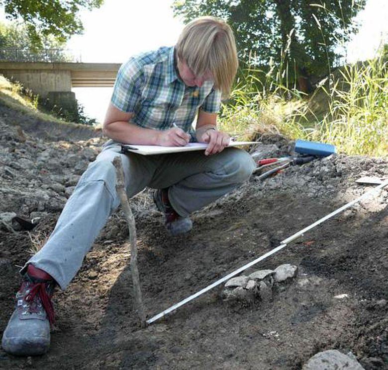 LWL-Archäologin Eva Cichy dokumentiert die Reste des zerdrückten Schädels. (Foto: LWL/Baales)