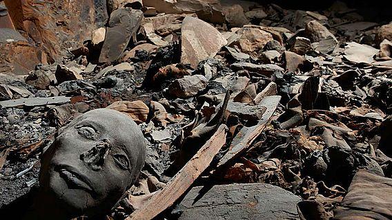 Mumifizierte Überreste zwischen Sargfragmenten, Stoffresten und Scherben
