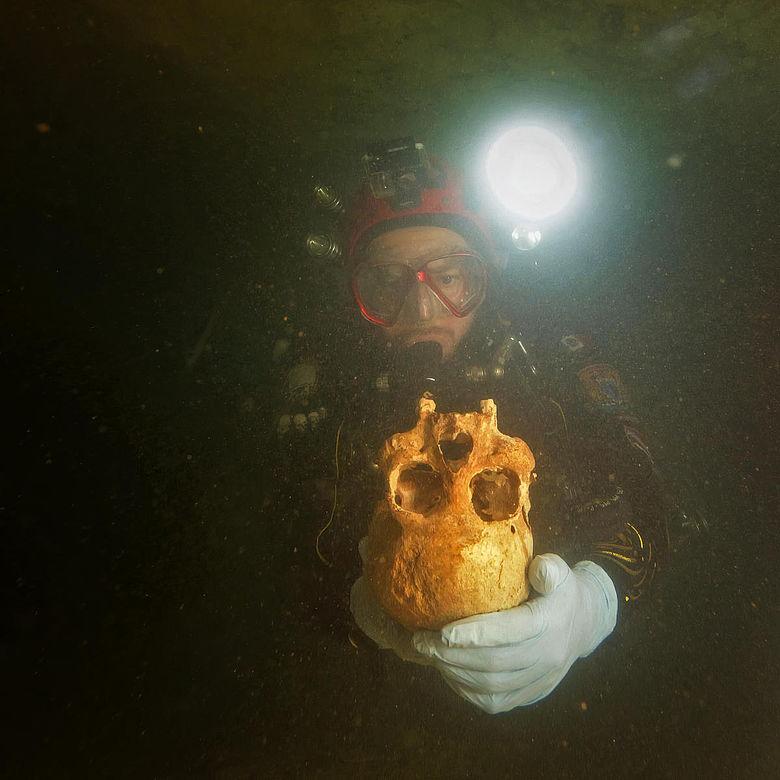 Taucher mit Schädel in der Chan-Hol-Höhle
