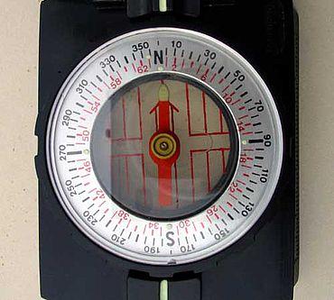 Abb. 2| Rezenter Peilkompass mit schwimmender Nadel und drehbarer Kompassrose. Die Nadelspitze weist immer auf magnetisch Nord. Der Leuchtpunkt westlich davon ist der angenommene Missweisungspunkt; stellt man die Kompassrose so ein, dass die Nadelspitze auf ihn zeigt, weist die N-Marke der Kompassrose in Mitteleuropa auf geographisch Nord – sofern die Korrektur stimmt.