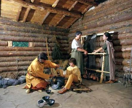 """Familie Borngräber im Innenraum des bronzezeitlichen Hauses, das nach Befunden aus der Ausgrabung """"Wasserburg Buchau"""" rekonstruiert wurde. (© Federseemuseum Bad Buchau)"""
