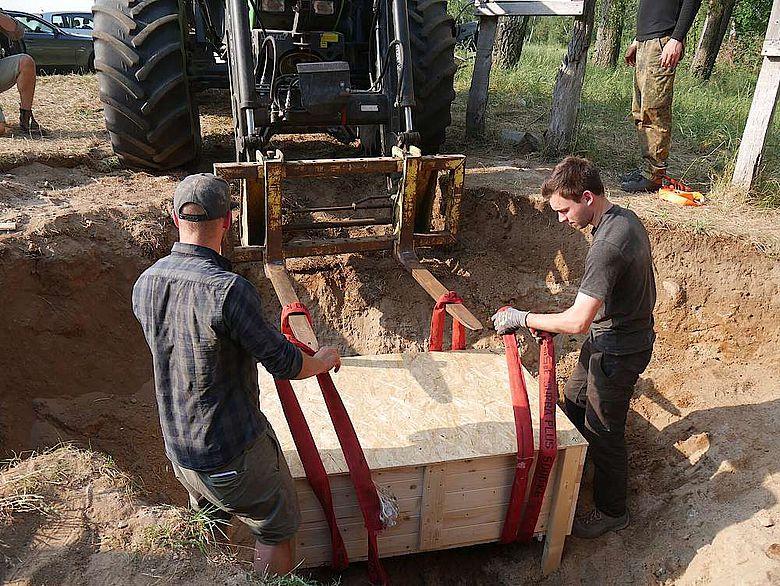 Die geschlossene Kiste wird an die Hebegabel des Traktors gehängt