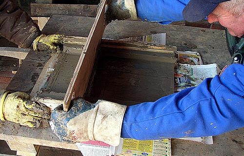 Handarbeit wie vor 2000 Jahren: Museumsmitarbeiter beim Streichen eines römischen Ziegels. (Foto: LWL/Hudemann)