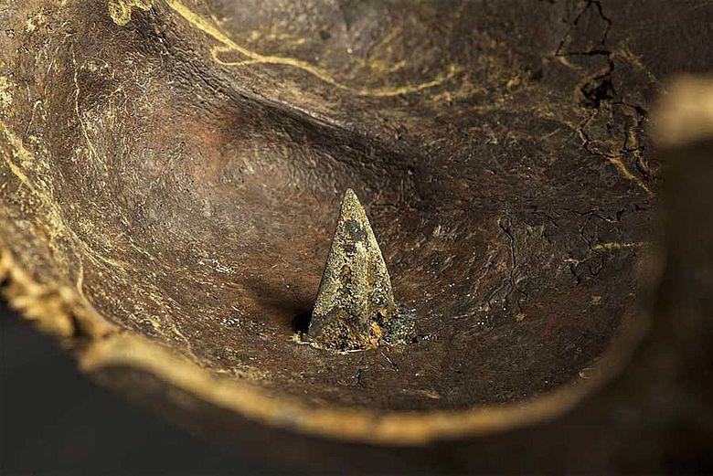 Bronzene Pfeilspitze in Schädel