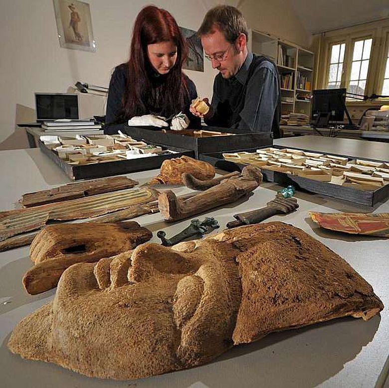 Der Archäologe Dr. Dennis Graen und die Archäologiestudentin Melanie Schulze studieren Grabbeigaben aus dem alten Ägypten, die derzeit an der Universität Jena neu bestimmt und kulturhistorisch eingeordnet werden. (Foto: FSU)