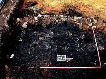 Erhaltene Überreste der Bohlenwand hinter der Frontmauer in Schnitt 9 auf der Schnippenburg. (Foto: S. Möllers, Stadt- und Kreisarchäologie Osnabrück)