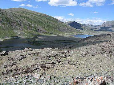 Landschaft am Olon-Kurin-Gol im mongolischen Altaj. Links am rechten Ufer des Sees ist das Camp der deutsch-russisch-mongolischen Grabungsmannschaft zu erkennen. (Foto: DAI Berlin)