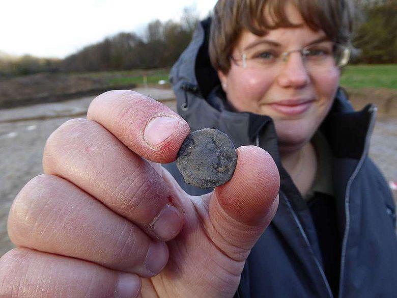 Grabungsleiterin Eva Manz präsentiert eine römische Münze