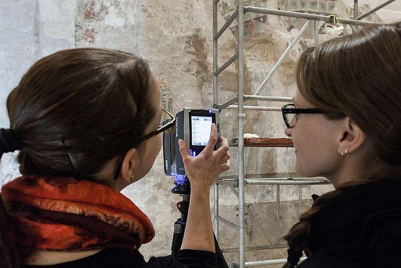 Studierende untersuchen mit einem 3D-Scanner Wandmalereien