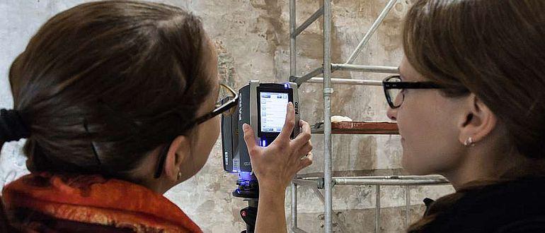 Studierende untersuchen mit einem 3D-Scanner Wandmalereien in der AULA der Universität Bamberg
