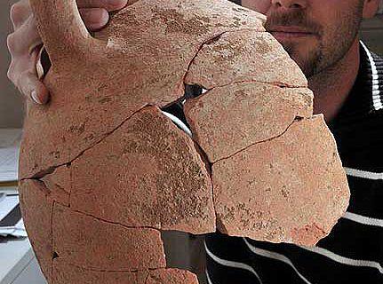 Dr. Dennis Graen von der Universität Jena mit einer bereits teilweise restaurierten Amphore, die bei der Grabung in Portugal gefunden wurde. (Foto: FSU)