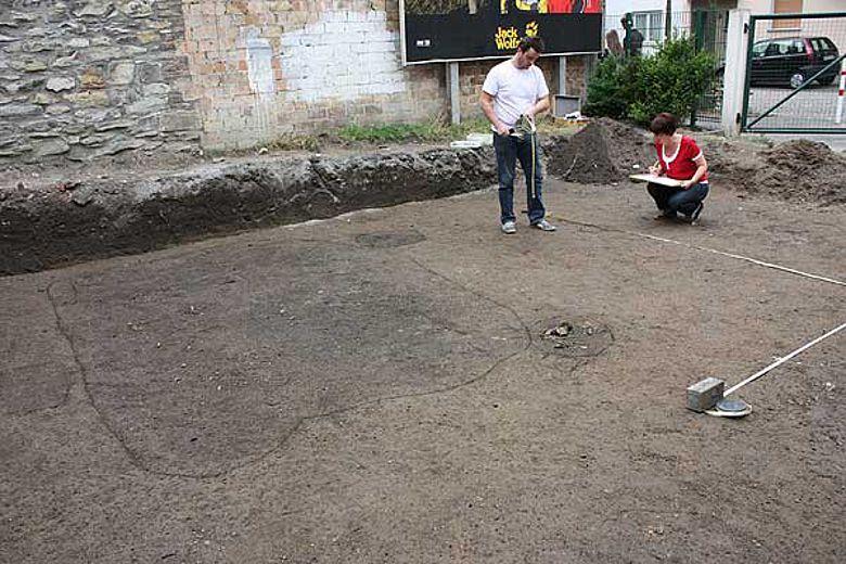 Die LWL-Mitarbeiter Tobias Nagler und Olga Heilmann vermessen und zeichnen das markierte Grubenhaus (links) - ein früheres Nebengebäude, das mit einem Webstuhl bestückt war. (Foto: LWL/S. Spiong)