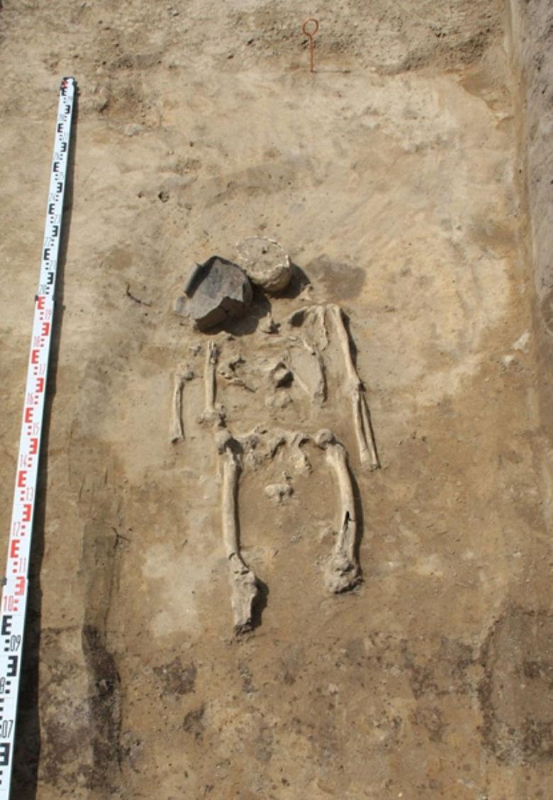 Ein freigelegtes Körpergrab mit einem Tongefäß als Beigabe (Foto: D. Megel, ABD Dressler)