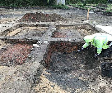 Deutlich sticht der rötlich verziegelte Lehm im einstigen Grubenhaus hervor