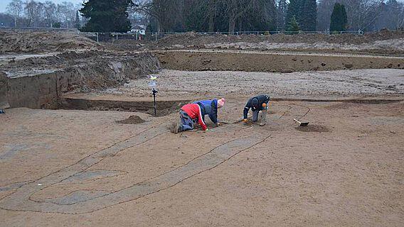 Der Graben als Hügeleinfassung des bronzezeitlichen Grabes stellt sich als dunkele Verfärbung dar