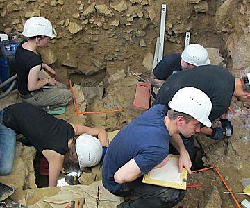 Vor dem großen Westprofil dringen die Studierenden auf dem Vorplatz der Blätterhöhle sicher und präzise in immer tiefere Schichten vor