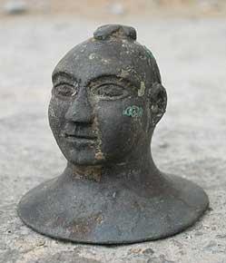 Büste eines kahlhäuptigen Mannes mit einem Phallus auf dem Kopf. Erstaunlich sind die Ausdruckskraft und der Detailreichtum dieser Figur. Bronze, römisch, 2.–3. Jh. n.Chr. (Foto: Kantonsarchäologie Zürich)