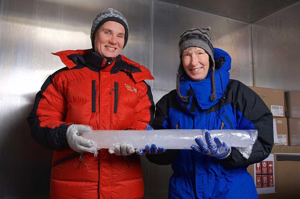 Forschende mit Eisbohrkern in Kältekammer