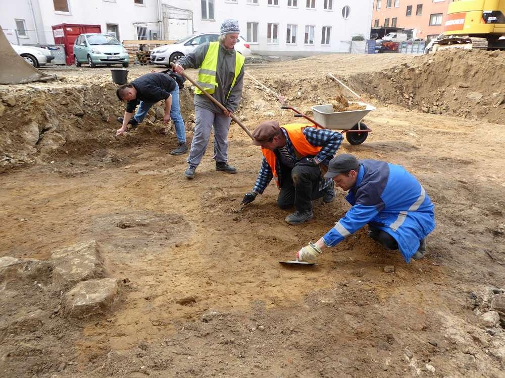 Grabungsteam säubert mit Kelle und Kratzer eine der aufgedeckten Flächen