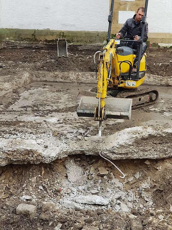 Mit Hilfe der zuständigen Baufirma wird die alte Bebauung des Innenhofs abgetragen