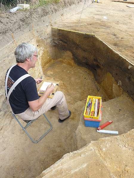 Dr. Martin Preuschoff entspannt sich beim Zeichnen einer mit viel Holzkohlresten verfüllten Abfallgrube. Hier entsorgten die Legionäre ihren Abfall aus den Mannschaftsbaracken. Die Grabung gefällt ihm so gut, dass er im September noch jeweils einen Tag in der Woche kommen will. (Foto: LWL/Tremmel)