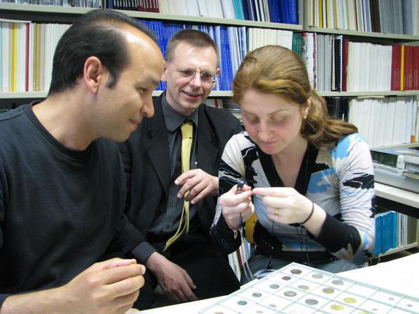 Mohammed Younis (v. l.) aus Ägypten, Stefan Heidemann aus Jena und Huda Subeh aus Syrien betrachten alte Münzen im Orientalischen Münzkabinett der Universität Jena (Foto: Friederike Enke/FSU)