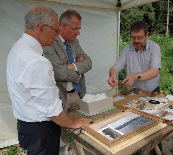 Mit großem Interesse lassen sich LWL-Direktor Dr. Kirsch (l.) und Ahlens Bürgermeister Ruhmöller (Mitte) von Grabungsleiter Dr. Grünewald die Funde von der Wallburg in Ahlen-Dolberg erläutern. (Foto: LWL/Burgemeister)