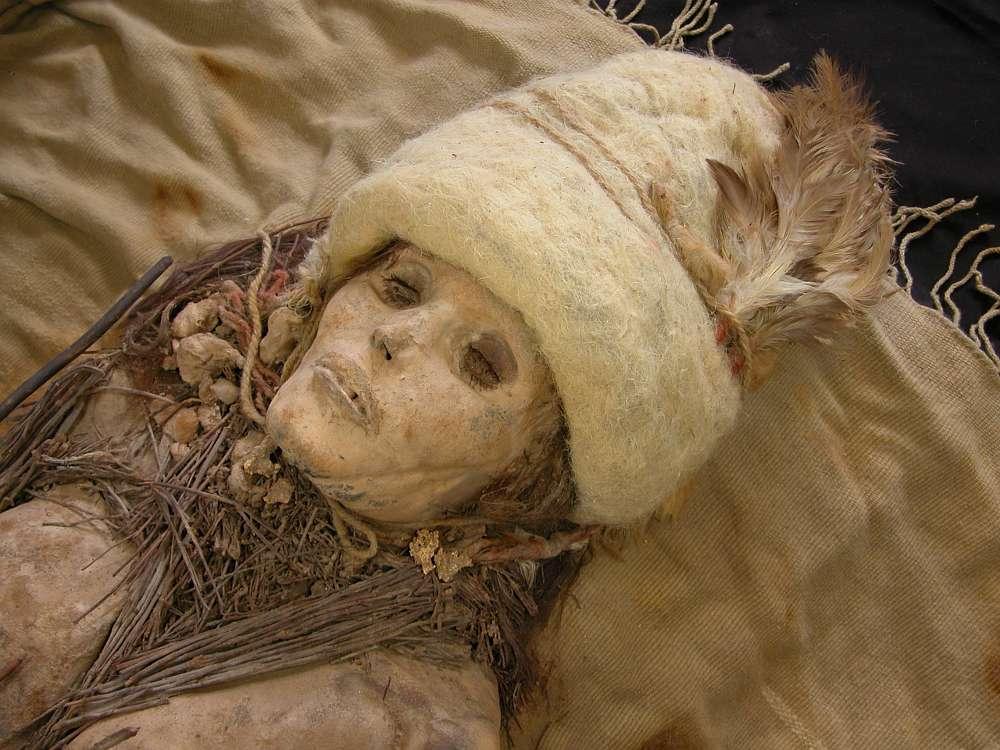 Kleine Käsebrocken sind als Grabbeigabe um den Hals der weiblichen Mumie verteilt